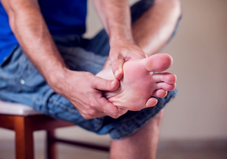 Man suffering from foot pain sitting on bench on street