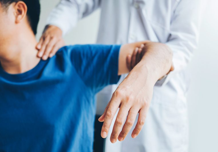 Physical Doctor consulting with patient about shoulder