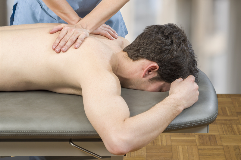 Physiotherapist, chiropractor giving a back massage to man patient